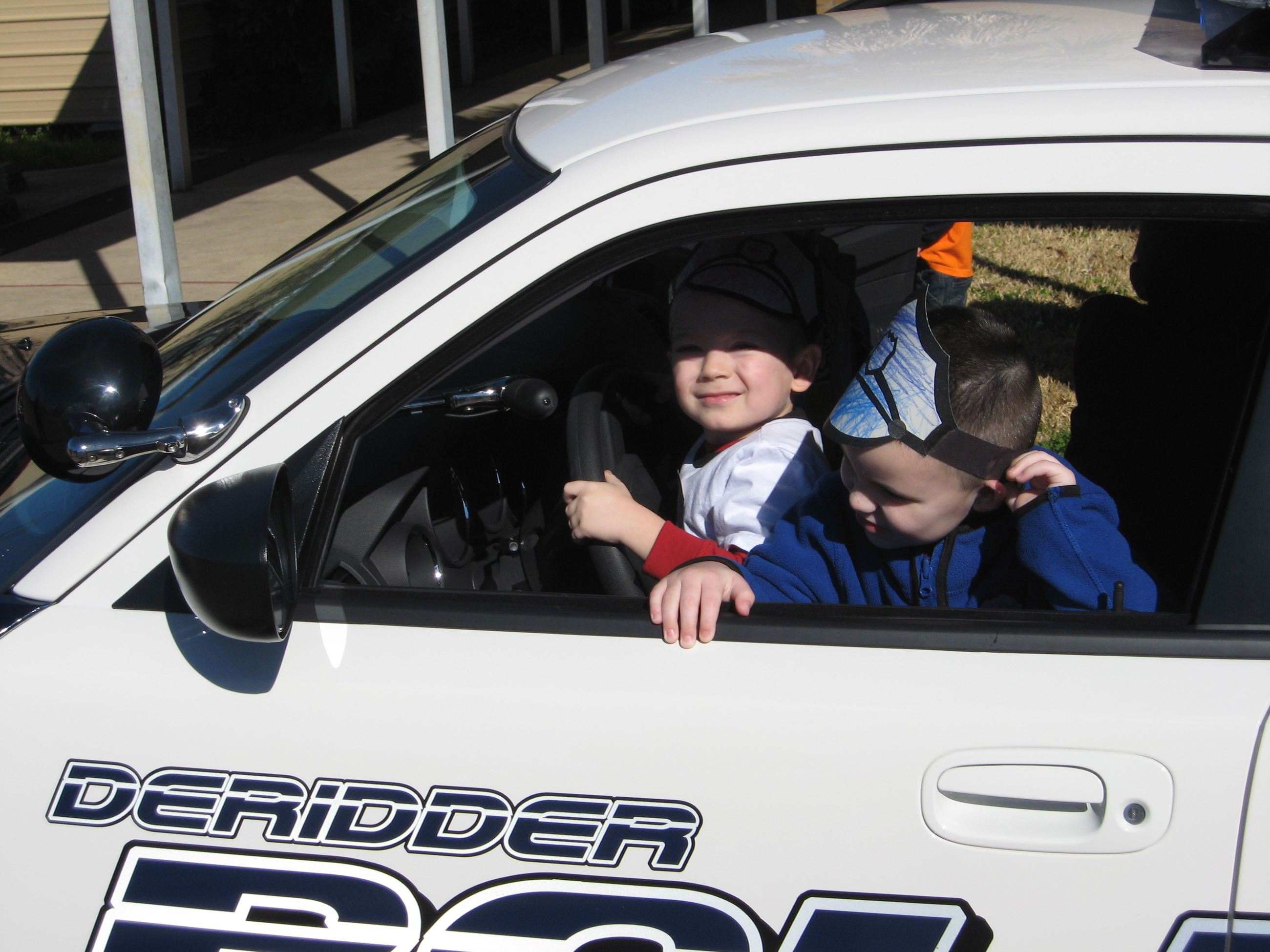 Children Sitting in the Driver's Seat of a Police C